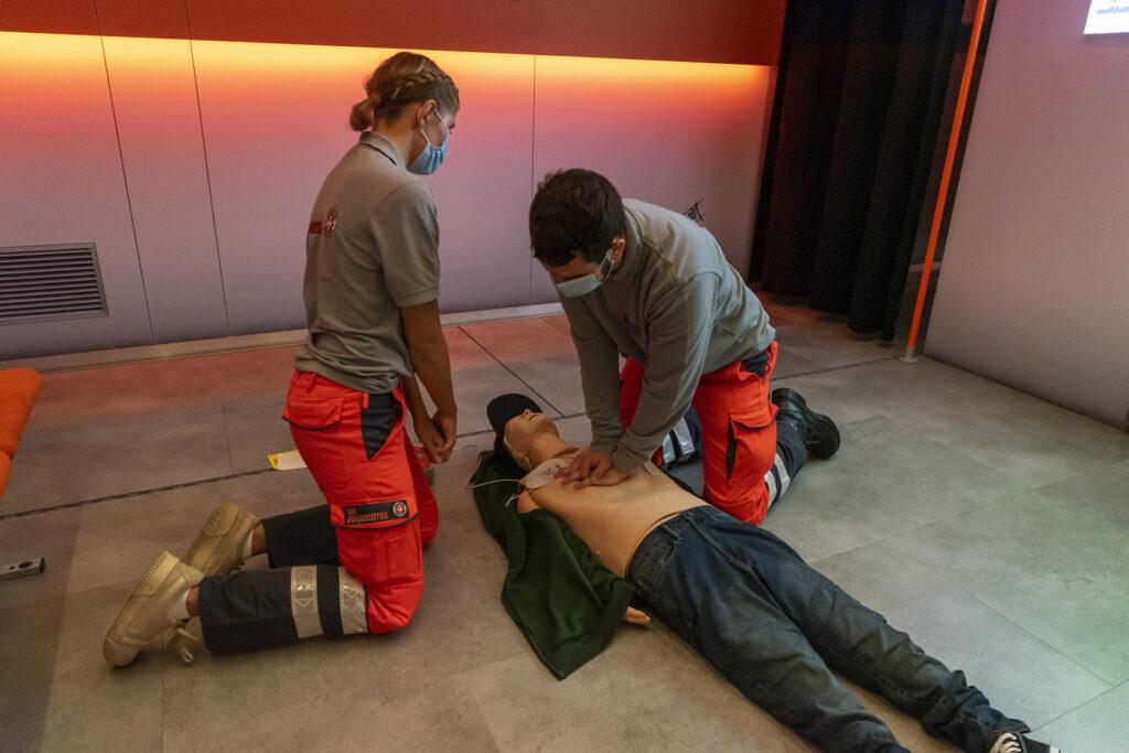 Die Johanniter Celina Schüler und Julian Zimmer machen vor, wie es geht: In der Simulation muss in einer U-Bahn ein Fahrgast wiederbelebt werden.